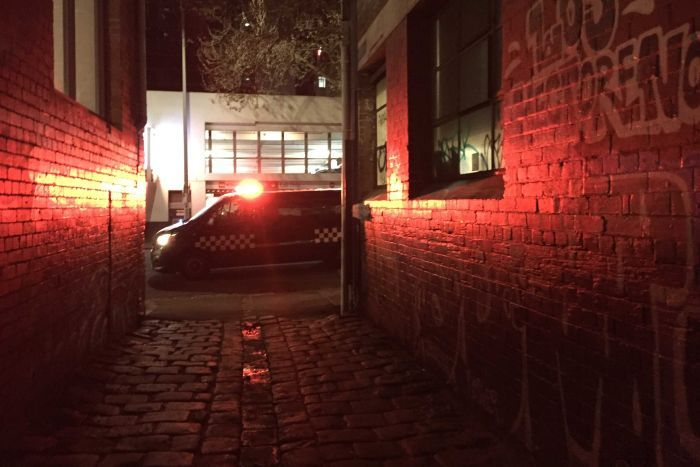 A police car drives past a Melbourne alleyway.