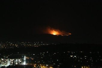 Look at a hill overlooking Canberra, and flames burning on the hills leave.