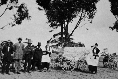 Seven men standing outdoors around a funeral card with a sign reading 'Off to bury Kaiser Bill'.