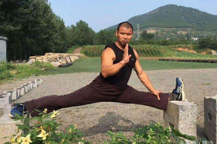 Shi Yanzi does a split outside against the backdrop of a mountain.