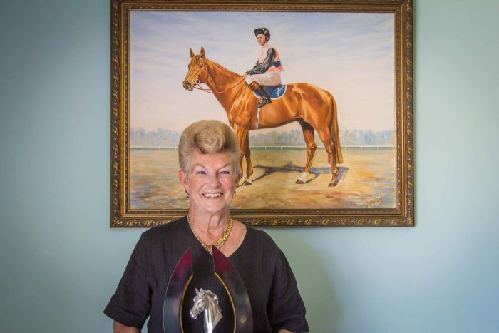 Woman holding a cup underneath a painting of her as a jockey.