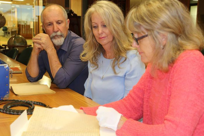 A man and two women examine historical documents.