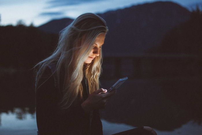 A woman's face is illuminated by her smart phone screen