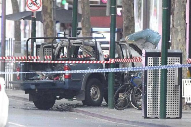 Burnt-out vehicle on the footpath surrounded by police tape