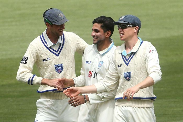 Jason Sangha is congratulated on a Shield wicket for NSW