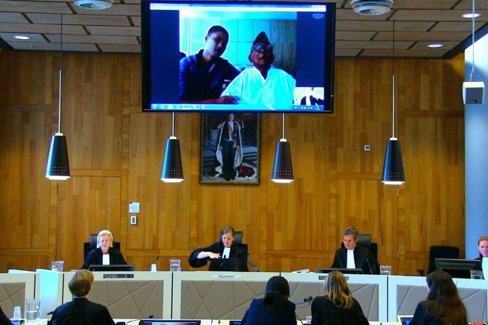 Four judges sit at a court bench, with a young man and an elderly gentleman appearing on a video screen above the desk.