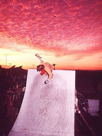 Bob Hastie skating on a ramp at sunset with a beautiful sky behind him.