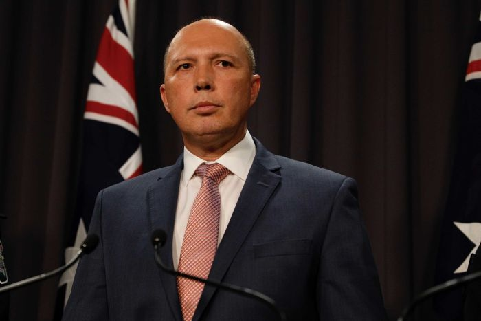 Peter Dutton looks into the distance with two Australian flags behind him