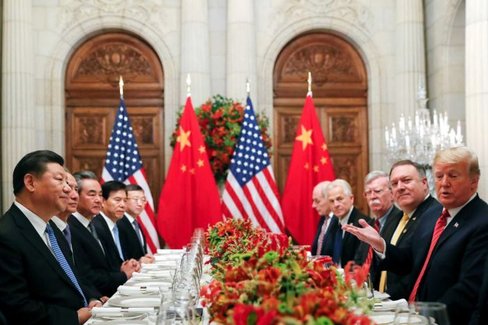 Donald Trump and Xi Jingping sit with US and Chinese officials at a table set for dinner.