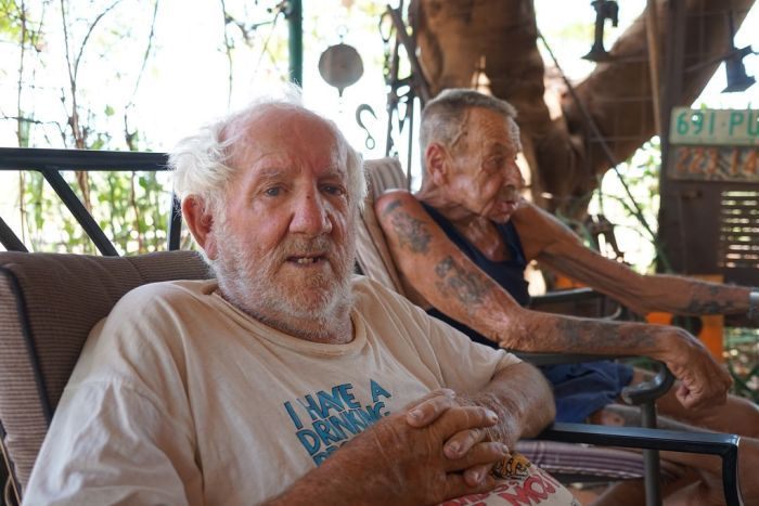 Two old men sit together on a couch in the shade.
