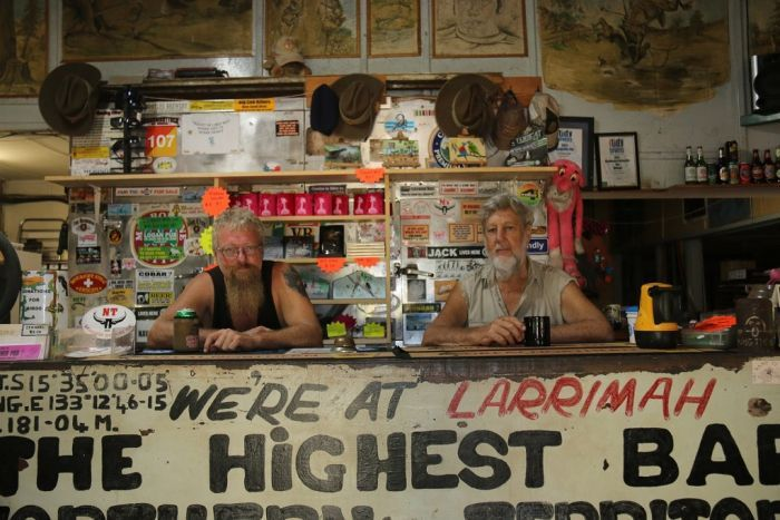Two men lean on the bar of an outback pub festooned with Australiana.