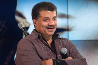 Neil deGrasse Tyson holds a microphone while at a fan event.