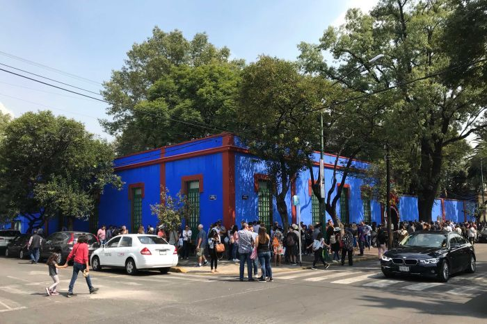 Hundreds of people lining up around the block of a bright blue building - Frida Kahlo's home in Mexico City.