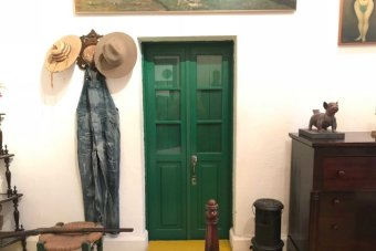A view inside Diego Rivera's bedroom. A green bathroom door is in the centre of the room. Beside it hang overalls and hats.