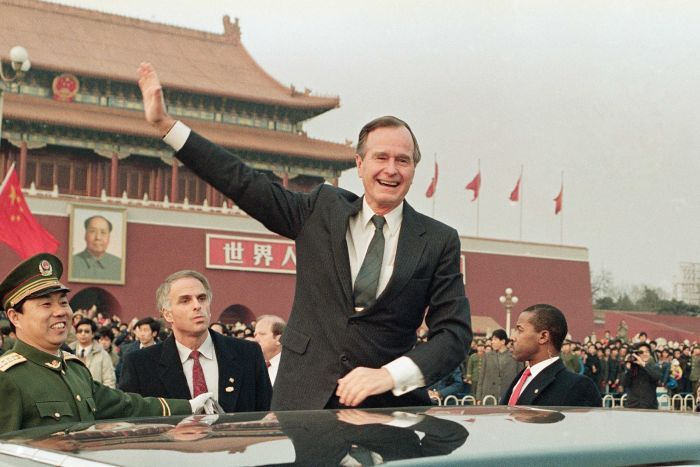 George HW Bush stands on a platform next to his motorcade waving to crowds in Beijing's Tianamen Square in 1989
