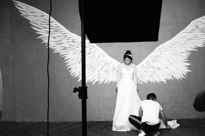 A bride poses for a prewedding photo shoot. She stands against a wall, in between a set of angle wings as a man fixes her dress.