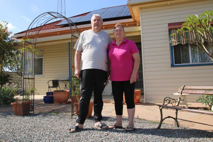 An older couple stand in the front garden of their home, which has solar panels on the roof