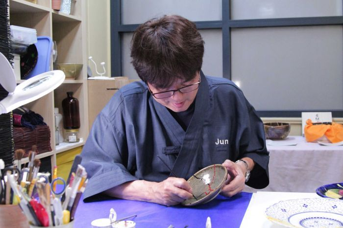 Jun uses a thin brush to carefully apply red paint on top of the dried lacquer.