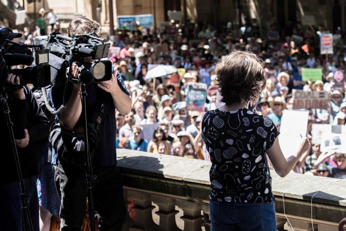 young girl speaking to audience with TV cameras filming her