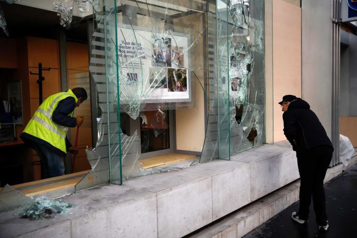A worker sweeps debris from a smashed glass storefront as a woman looks on.