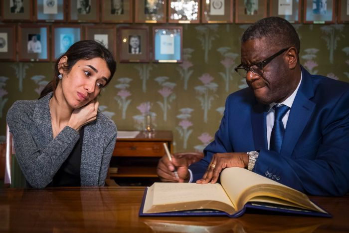 Nadia Murad and Dr Denis Mukwege sign a guestbook at the Nobel Institute in Norway with portraits lined up on a wall behind them
