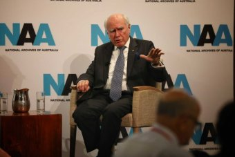 Former Prime Minister John Howard wears a dark suit with blue tie while sitting in a chair while gesturing with hand.