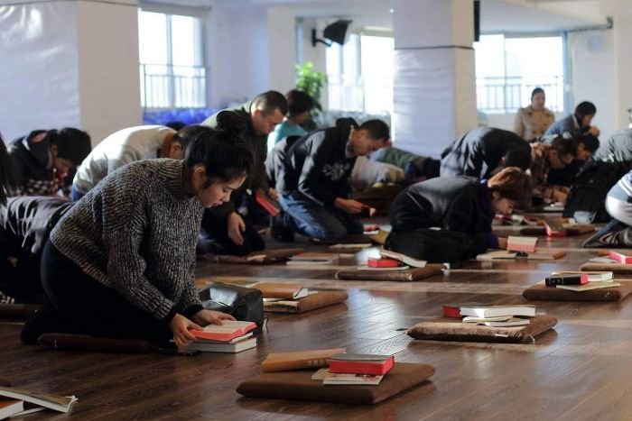 Worshippers at the Early Rain Covenant Church in Chengdu pray on the floor, bowing with bibles and pillows.