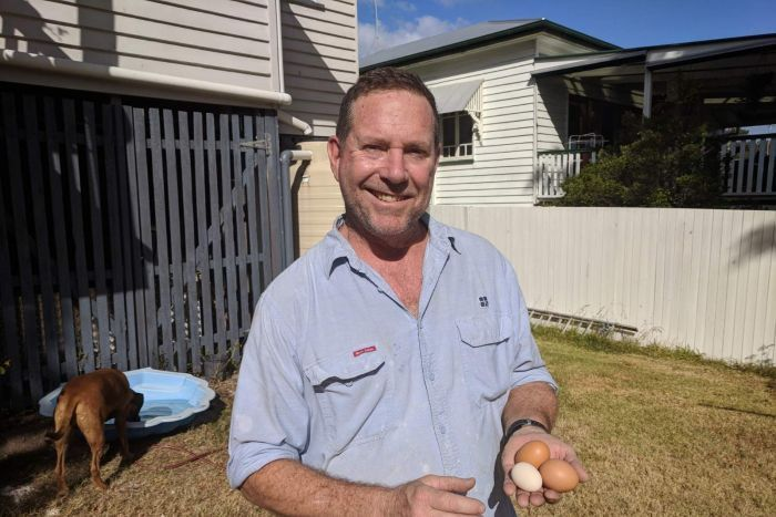 Man standing in a suburban backyard, smiling, holding three eggs