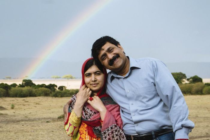 Malala Yousafzai and her father Ziauddin posing for a photo in the country with a rainbow in the background