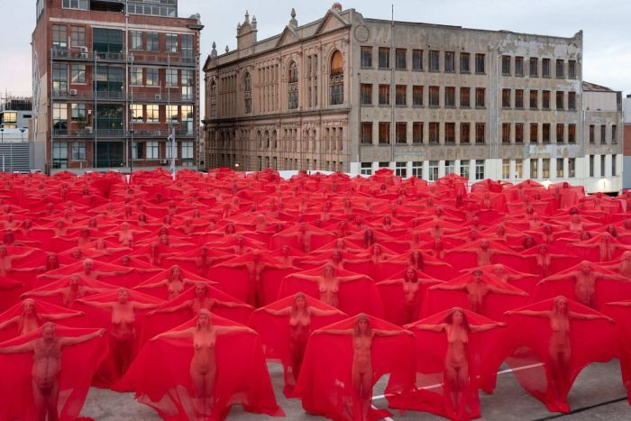 Naked people standing in  a carpark under red veils.
