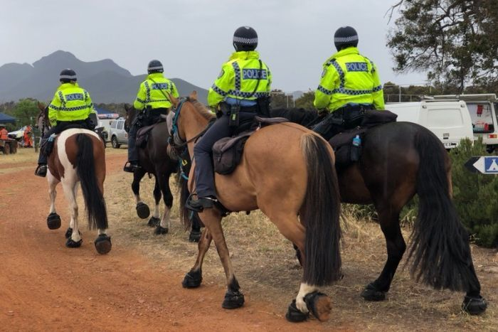 Four police officers riding away on large horses.