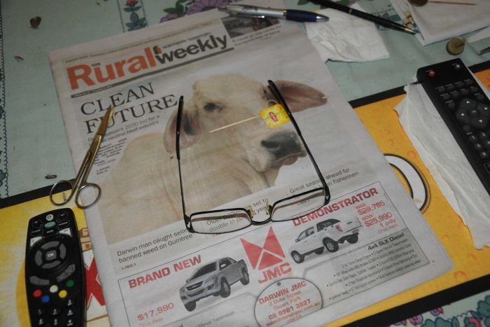 A pair of reading glasses and scissors on a copy of Rural Weekly.