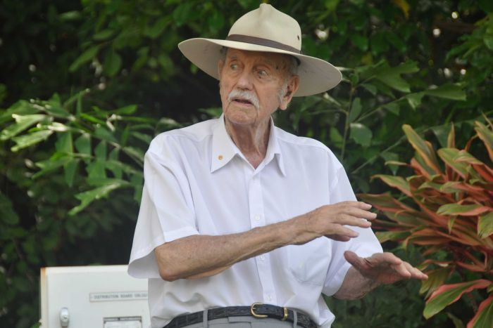 A man speaking to a crowd with a backdrop of tropical plantlife.