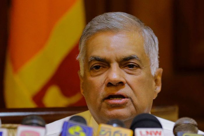 Sri Lankan Prime Minister Ranil Wickremesinghe speaks in front of a row of microphones with the Sri Lankan flag behind him