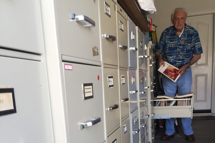 A elderly man holds up a fire safety manual while standing beside a large filing cabinet.
