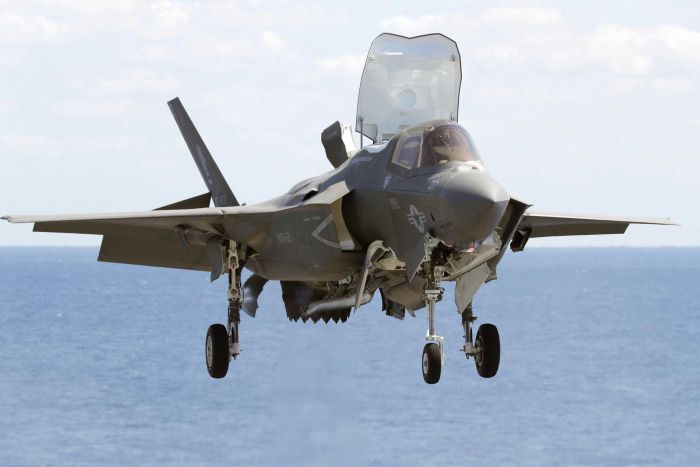 A US military F-35B fighter jet is photographed approaching an aircraft carrier in the western Pacific.