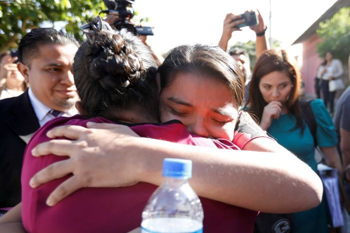 Imelda Cortez is hugged by a supporter as she leaves court surrounded by a media a throng.