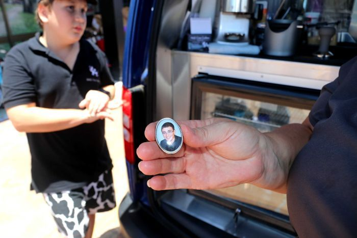 A locket photo is being held up in front of a coffee van.