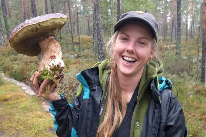A woman wearing hiking attire smiles while holding up a comically-large mushroom.