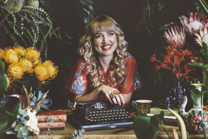 Colour photo of writer Holly Ringland sitting as a desk with a type writer and surrounded by flowers.
