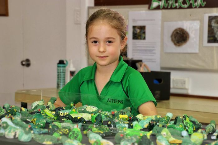 A girl in a green school uniform in front of a glass case with lots of small western ground parrot figures inside.