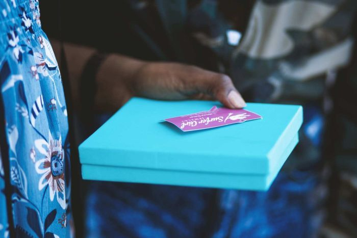 Woman holds a gift in a square box with a gift card sitting on top.
