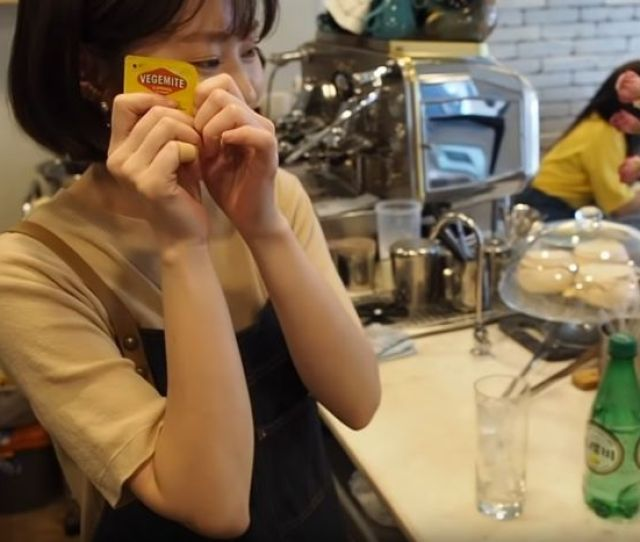 A Korean Staff Member At The Old Cap Cafe In Seoul Holds A Small Container Of