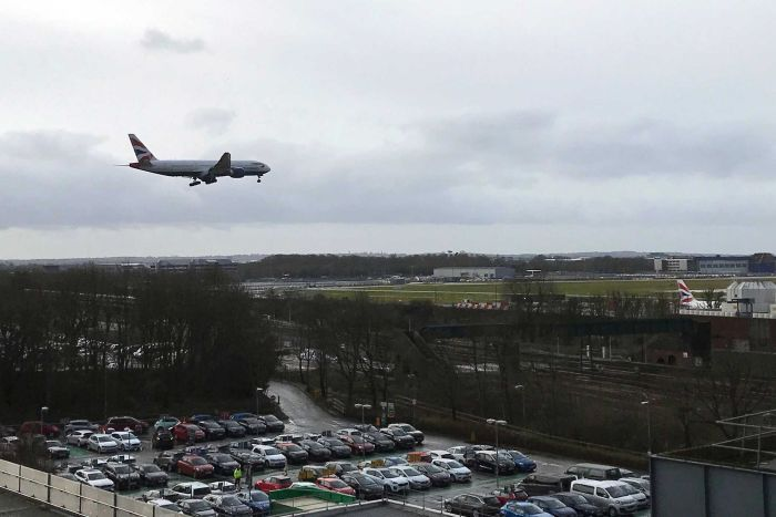 A plane flying over the Gatwick airport and a carpark.