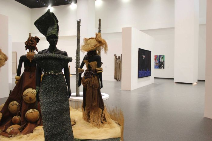 An exhibition space shows three mannequins wearing traditional African textiles.