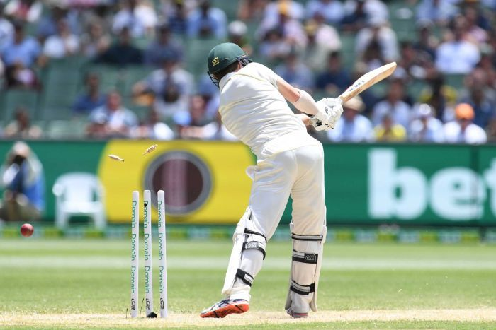 Australian batsman Travis Head is seen from behind, swinging his bat as the ball hits his stumps during a Test at the MCG.
