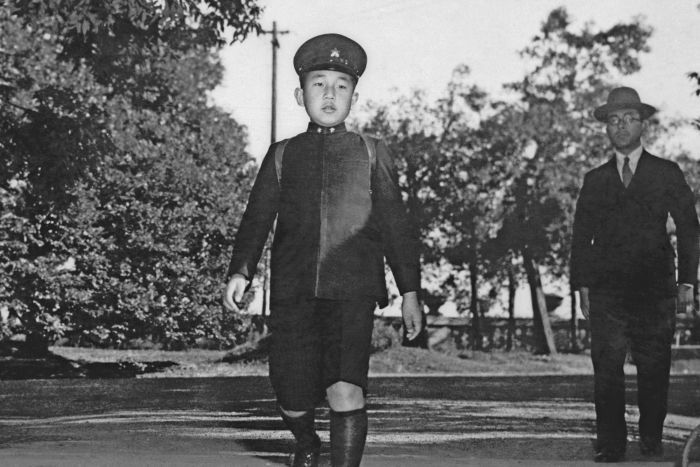 A black and white image of Emperor Akihito showing him marching in military uniform