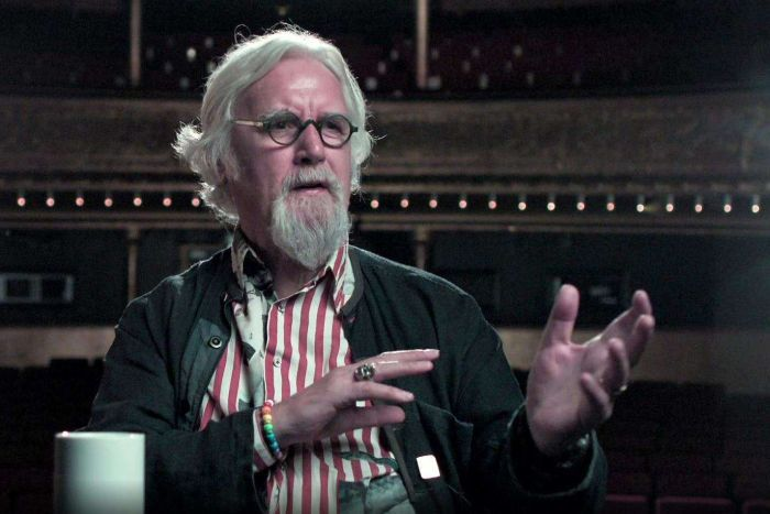 Sir Billy Connolly raises his hands as he is interviewed