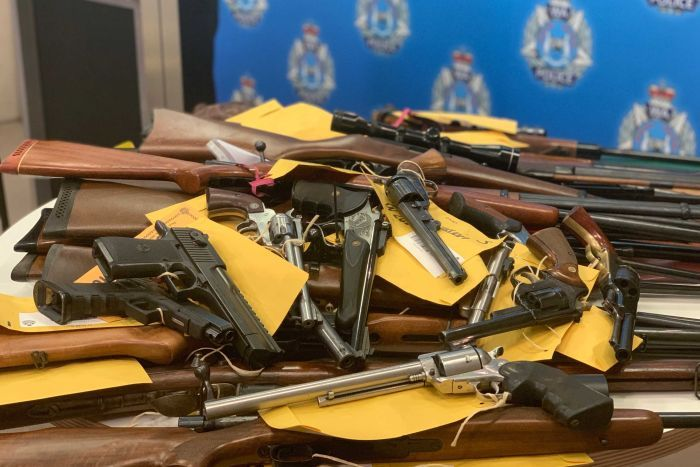 Pile of pistols and rifles on table with police crest in the background