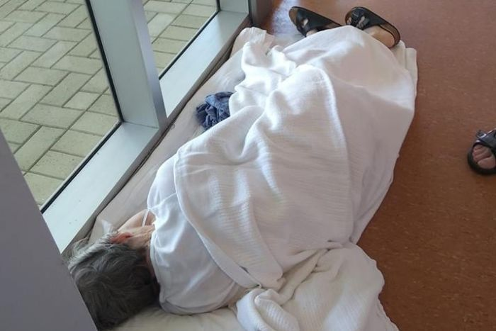 A woman lies on the floor of a hospital corridor covered in a white blanket.